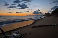 A beautiful sunset illuminating one of Kauai's soft-sand, south shore beaches near the town of Waimea.