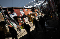 Miners walk on the muddy, half-frozen streets, with a sewage ditch in the middle, in La Rinconada, Peru, 5 August 2012. During the last decade, the rising price of the gold has attracted thousands of people to La Rinconada in the Peruvian Andes. At 5300 metres above sea level, nearly 50.000 people work in the gold mines and live in the nearby colonies without running water, sewage system or heating service. Although the work in the mines is very dangerous (falling rocks, poisonous gases and a shifting glacier), the majority of miners have no contract and operate under the cachorreo system - working 30 days without payment and taking the gold they supposedly find the 31st day as the only salary. In spite of a demaged environment, caused by mercury contamination from the mining and the lack of garbage disposal, people continue to flock to the region hoping to find their fortune.