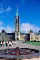 "Parliament Buildings on Parliament Hill, in the City of Ottawa, Ontario, Canada - Tourists visiting ""Centennial Flame"" (lit 1967) in front of Centre Block with Peace Tower (built 1865 - 1927)"