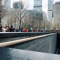 Tourists peer into a waterfall marking the former location of the World Trade Center North tower at the 9/11 Memorial Plaza in Manhattan, New York on Sunday, April 29, 2018. (Photo by James Brosher)