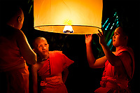 Three traditional novice monks lighting a floating paper lantern during Loy Krathong festival at Wat Phan Tao temple, Chiang Mai Thailand