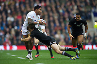 Manu Tuilagi of England offloads as he is tackled by Conrad Smith of New Zealand during the QBE Autumn International match between England and New Zealand at Twickenham on Saturday 01 December 2012 (Photo by Rob Munro)