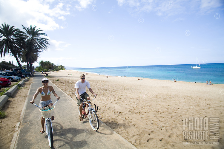 Young man and woman riding a cruiser bikes on the scenic North Shore bike path