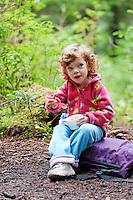 Three year old girl eating in campsite, Boardman Lake, Cascade Mountains, Washington, USA