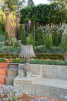 Tiled garden bench surrounds a sunken deck patio, with beautiful Moorish style landscaping, with garden lamp to create outdoor room feeling, Agapanthus blue flowered bulbs, ornamental grasses, etc, in several levels