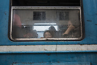 Una bambina guarda dal finestrino del treno <br />