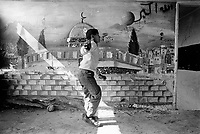 Palestine. West Bank. Balata Camp. A boy plays football indoor near a drawing of Al-Aqsa mosque painted on the wall. Al-Aqsa Mosque is the third holiest site in Sunni Islam. Balata Camp is the largest refugee camp in the West Bank. © 1991 Didier Ruef