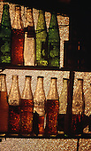 Itaparica Island, Brazil. Coca-Cola and other soft drinks bottles on two shelves in front of dappled glass. Bahia State.