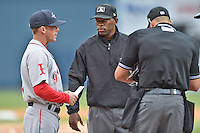 Greenville Drive manager Darren Fenster (3) talks with first base umpire Chris Lloyd before a game between the Asheville Tourists and the Greenville Drive on April 16, 2015 in Asheville, North Carolina. The Tourists defeated the Drive 5-4. (Tony Farlow/Four Seam Images)