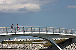 A bridge over the bay at the lake front with two site seers walking over it to the peninsula.  Milwaukee and Lake Michigan
