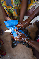 Africa, DRC, Democratic Republic of the Congo, South Kivu, Kamanyola. Women for Women project. WFW Kamanyola co-op and lifeskills training. Women making medicinal soap to sell.  Kiza Mugala carving the soap.