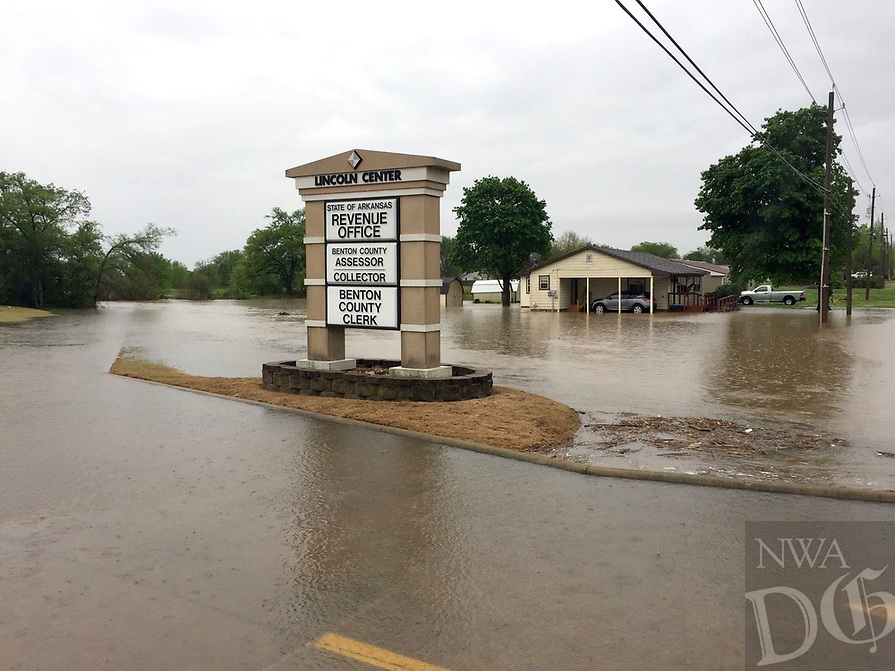 Graham Thomas/Herald-Leader<br /> The parking lot of the state revenue office in Siloam Springs was flooded after heavy rain Wednesday morning.