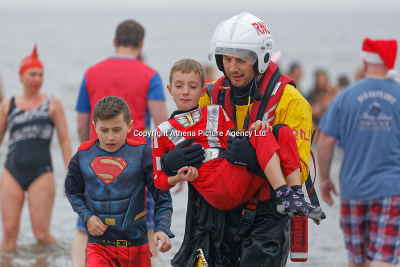 Pictured: A young boy is carried back to safety by an RNLI rescuer. Tuesday 25 December 2018<br /> Re: Hundreds of people take part in this year's Porthcawl Christmas Swim in south Wales, UK.