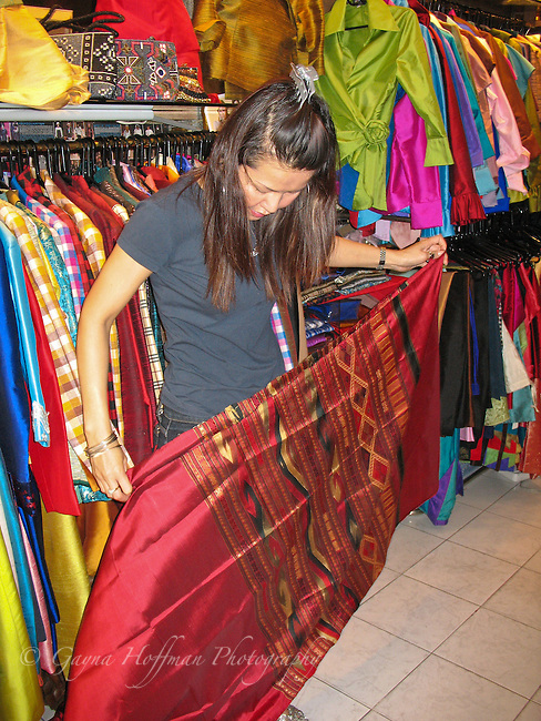 Woman holding up red silk cloth in silk store. Bangkok, Thailand
