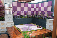 Creating an outdoor room with sense of enclosure with patterned wall, Zen feel post and deck, trellis covering, Japanese maple tree Acer palmatum, raised beds with purple alliums flowers and heuchera perennials for a color coordinated, harmonious backyard landscaping designed by Takumi Awai