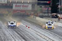 Mar 29, 2014; Las Vegas, NV, USA; NHRA funny car driver Robert Hight (left) races alongside Ron Capps during qualifying for the Summitracing.com Nationals at The Strip at Las Vegas Motor Speedway. Mandatory Credit: Mark J. Rebilas-