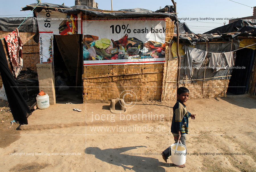 INDIA, New Delhi, forced shifted slum dweller at Slum Naglamachi at outskirts of Dehli, the people are mosty dalits, hut with old advertisement banner 10 percent cash back  / INDIEN  Neu Delhi , <br /> zwangs umgesiedelte Dalits im Slum Naglamachi am Stadtrand von Dehli