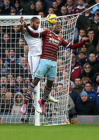 Sunday 07 December 2014<br /> Pictured L-R: Ashley Williams of Swansea heads the ball over Cheikhou Kouyate of West Ham<br /> Re: Premier League West Ham United v Swansea City FC at Boleyn Ground, London, UK.