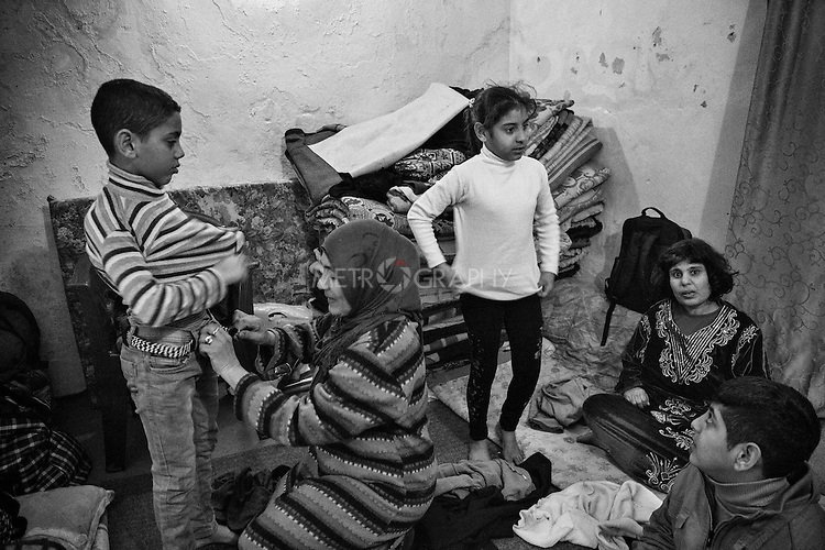29.1.2015 Kirkuk,Iraq. Widad Fadhil, 47 years old is seen helping the kids to prepare before going to school.