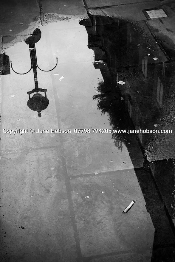 London, UK. 02.02.2020. Reflections in a puddle, Soho, London, UK. Photograph © Jane Hobson.