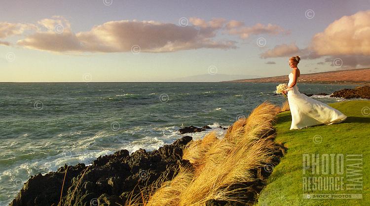 At the end of the day, a bride looks out at Kauna'oa Bay from the grounds of the Mauna Kea Beach Hotel, Kohala Coast, Big Island.