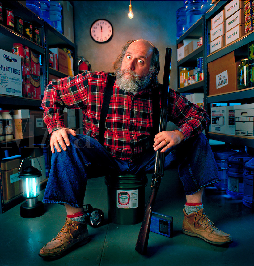 At a few minutes before midnight, this man sits in his basement fallout shelter waiting for a Y2K disaster to strike. He has food, water and fuel stocked on shelves, a battery operated lantern and a shotgun. United States.