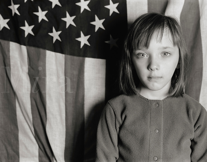 Young Girl standing with an American Flag.