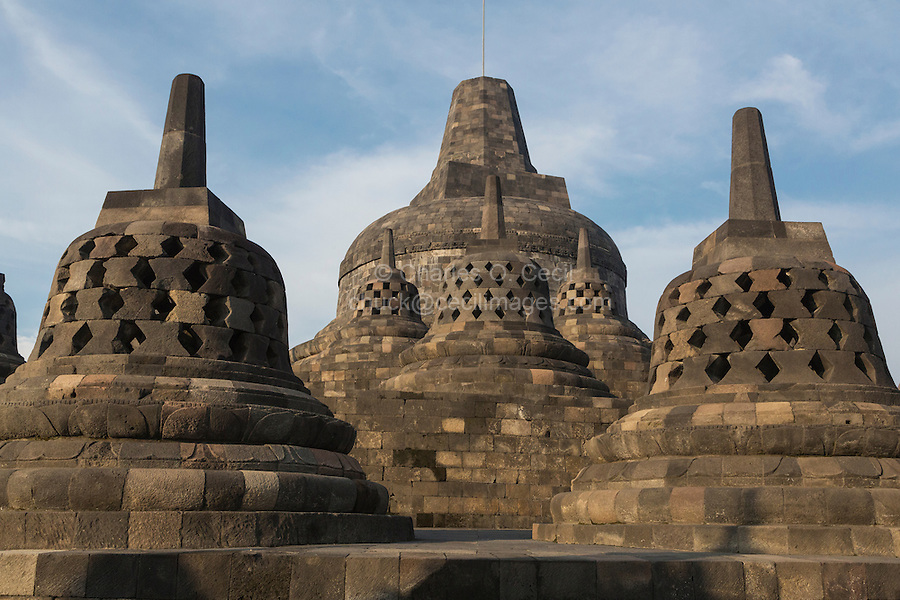 Borobudur, Java, Indonesia.  Approaching the Topmost Stupa.  The diamond-shaped holes in the three closest stupas symbolize the passions that still linger as men rise toward Nirvana.  The top two, with square-shaped openings, symbolize the overcoming of passions as one approaches Nirvana.