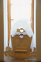 A rocking baby cot with carved heart shapes and a fabric cover at the Hotel & Spa Rosa Alpina in the Dolomites