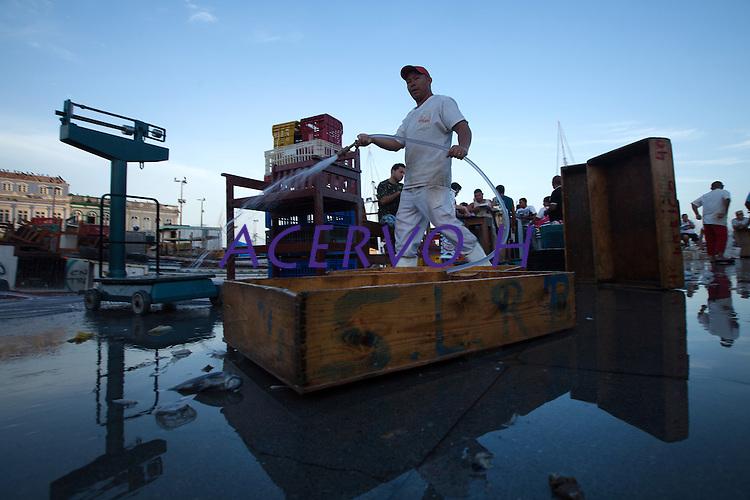 Feirante lavando a calçada da feira do ver-o-peso, no final do expediente. Local: Belém-PA, Data: 03/11/2012, Foto: Ana Mokarzel