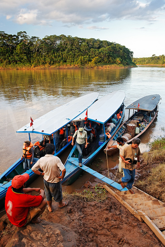 Tourists disembarking tour boat on Tambopata River, Peru