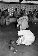 """January 1976, Calcutta, India --- Mother Teresa bends down to play with an infant lying on the floor. The first Home for the Dying opened in 1952 and was a free hospice for the poor. Mother Teresa (Agnes Gonxha Boyaxihu) the Roman Catholic, Albanian nun revered as India's """"Saint of the Slums"""", was awarded the 1979 Nobel Peace Prize. --- Image by © JP Laffont"""