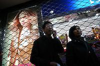 CHINA. Shanghai. A couple standing near an advertisement. 2008.