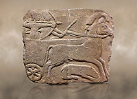 Photo of Hittite monumental relief sculpted orthostat stone panel. Limestone, Karkamıs, (Kargamıs), Carchemish (Karkemish), 900-700 B.C. Hunting carriage.  Anatolian Civilisations Museum, Ankara, Turkey.<br /> <br /> Two human figures; one handling the carriage, the other throwing arrows. Both figures are wearing a headdress shaped like a skullcap. The dagger at the waist of the figure throwing arrow draws attention. There is an animal between the legs of the horse having an aigrette over its head. <br /> <br /> Against a brown art background.