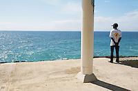 Dominican Republic. Distrito Nacional Province. Santo Domingo. A black man looks at the Carribean Sea.  © 2006 Didier Ruef