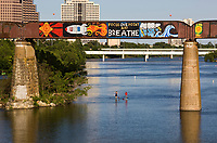 """SUP stand up paddle board couple row under the """"Focus One Point And Breathe"""" colorful graffiti painting with a USA space rocket on a the railroad bridge over Lady Bird Lake, overlooking the Austin skyline."""