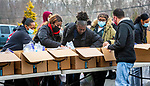 WATERBURY, CT-011421JS01- Alderman George Noujaim and member of Our Lady of Lebanon Maronite Catholic Church in Waterbury, sets out boxes and talks with residents during a free giveaway Thursday in the church parking lot. The giveaway, was organized by New Opportunities, Inc., and World of Giving in Waterbury to gather people and help them out with donated items from Amazon, but also inform them of the services offered by the agency. <br /> Jim Shannon Republican-American