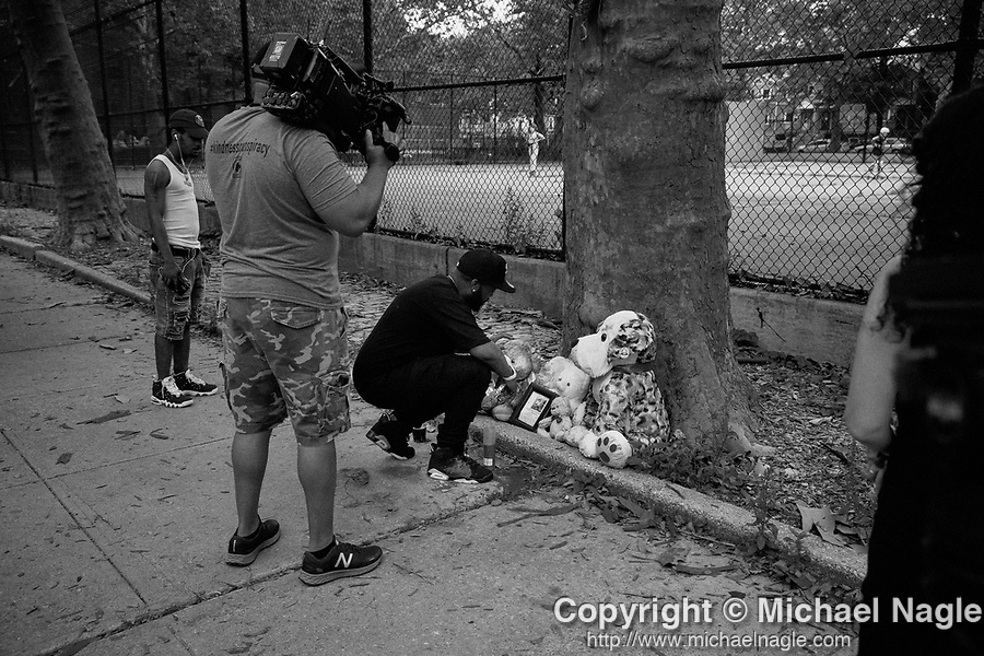 BROOKLYN, NY — JULY 13, 2021: Christian Braxton, News 12 Brooklyn reporter, documents Stanley, the godfather of 1 year-old Davell Gardner, Jr., who was shot while sitting in his stroller at a barbecue a year ago today, looking at a memorial at Raymond Bush Playground in Brooklyn, NY on July 13, 2021. Two suspects were charged in May, in what investigators believe to be part of a feud between rival gangs. Photograph by Michael Nagle