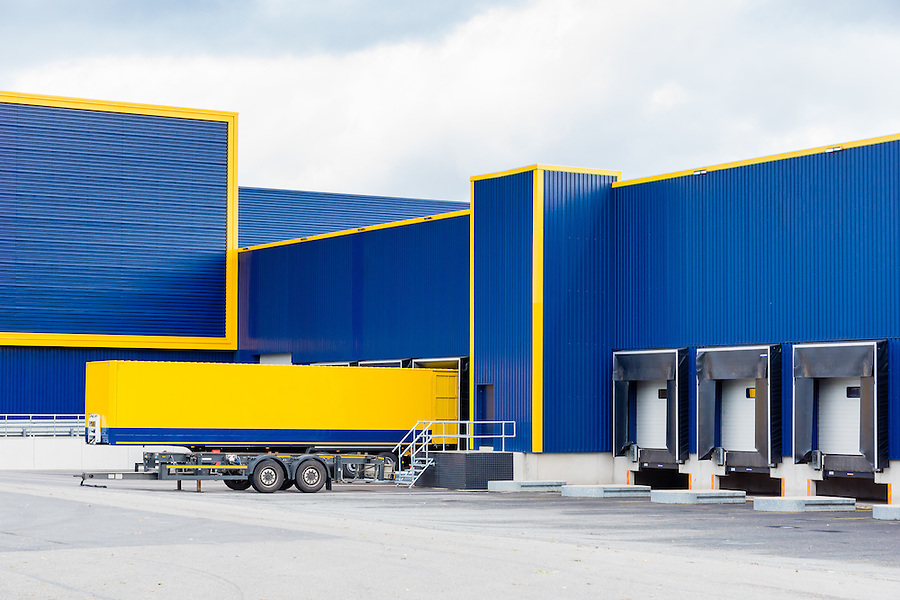 warehouse painted yellow and blue with a trailer in front
