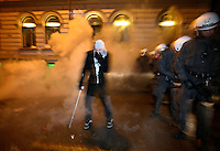 A protester on crutches hobbles away as he is being engulfed in some sort of gas. Pro-Palestinian protesters clashed with police as they held another demonstration against Israel in the Norwegian capital Oslo. Violent clashes lasted for hours  in the centre of Oslo. Israeli forces began a series of air strikes on the Gaza Strip on the 27th of December in retaliation against Hamas rockets fired into Israel. After eight days of bombardment, leaving over 400 Palestinians and four Israelis dead, Israeli tanks launched a ground invasion on the 4th of January.