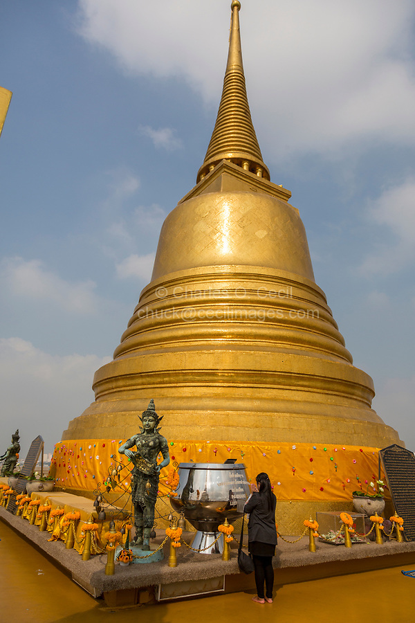 Bangkok, Thailand.  God of the Area of Wat Saket (Phu Khao Thong), the Golden Mount, Stands Guard at Corner of Golden Chedi on top of the Mount.