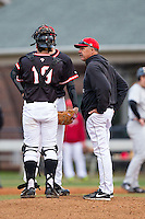 Davidson Wildcats head coach Dick Cooke (25) has a chat on the mound with Chris Dyer (19) and Clark Beeker (26) during the game against the Wake Forest Demon Deacons at Wilson Field on March 19, 2014 in Davidson, North Carolina.  The Wildcats defeated the Demon Deacons 7-6.  (Brian Westerholt/Four Seam Images)