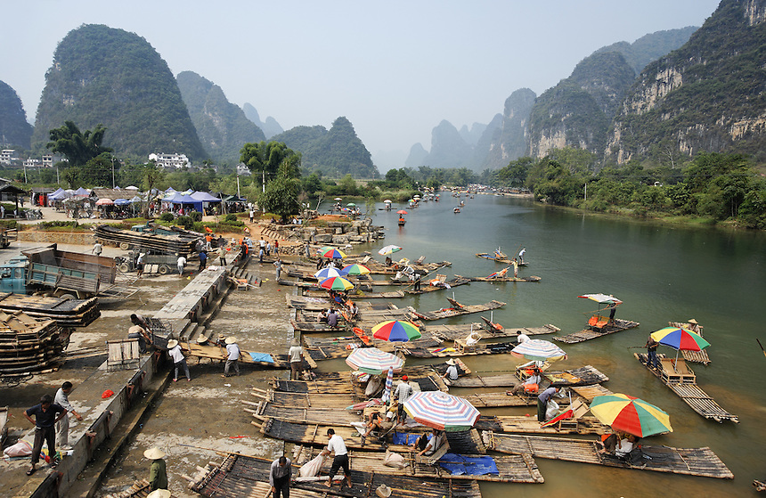Bamboo tourist rafts being pulled out of Yulang River and put on trucks, Yangshuo, Guanxi, China