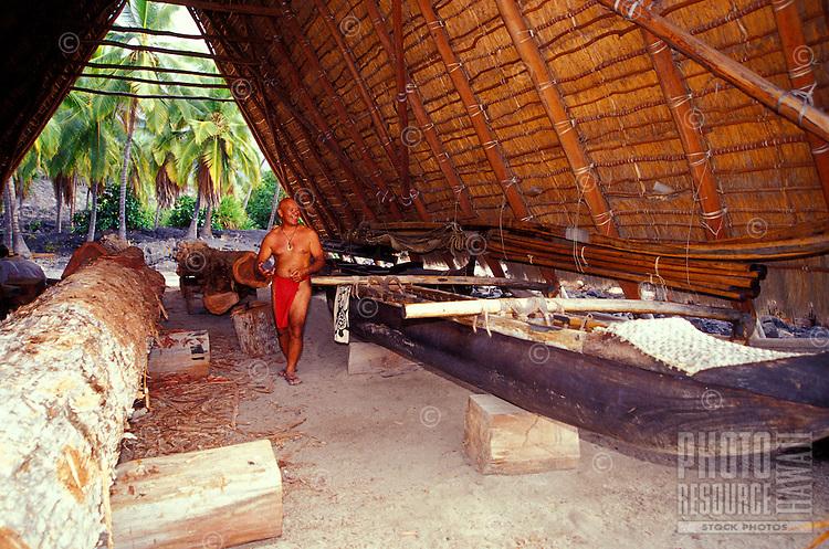 Hawaiian man carving a traditional Hawaiian sailing canoe at Puu Honua Honaunau, also known as city of refuge, a National historical park on the Big island