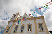 Itaparica Island, Bahia State, Brazil. Itaparica town. Restored colonial baroque church, colourful bunting. Blue sky and white clouds.