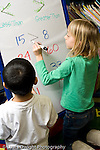 """Education Elementary school Grade 1 mathematics dry erase board with """"greater than"""" """"less than"""" activity two students working one boy and one girl horizontal"""