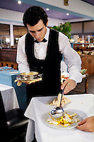 A waiter spoons broth over fish as he serves bouillabaisse to diners at restaurant Le Calypso, Marseille, France, 25 August 2012. Bouillabaisse is a traditional Provençal fish stew originating from Marseille.