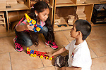 Education Preschool 3-4 year olds boy and girl talking and playing together in block area holding airplane constructions they made from connecting plastic pieces