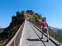 Tourists make the long climb up the bridge to Civita di Bagnoregio, Ital