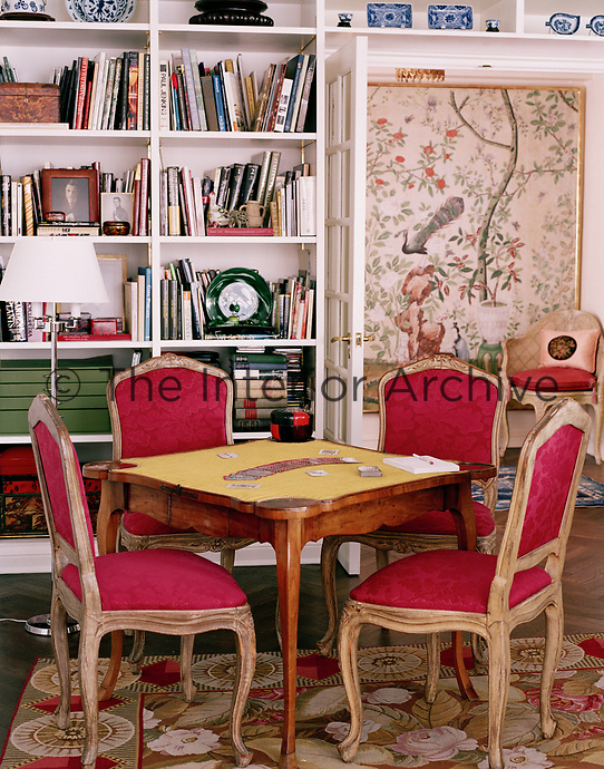 Mary Jane Pool hosts weekly bridge matches around her 18th century French card table. As with the rest of her home, the antique table is paired alongside items that reflect her wide-variety of tastes and interests. The rug is suitably floral, while a giant, modern built-in bookcase houses a vast array of books.